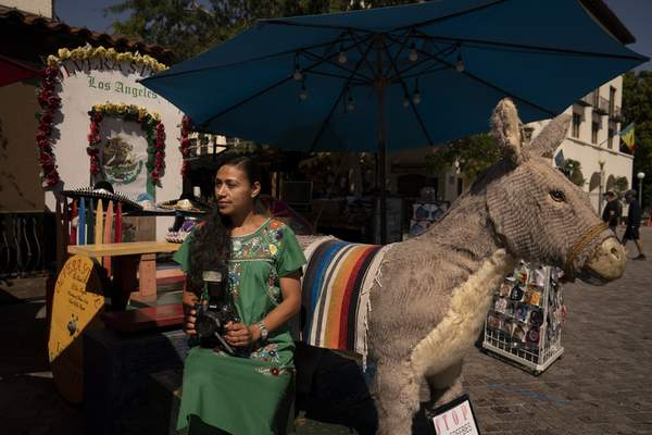 Photographer Carolina Hernandez, 39, sits for a photo next to a stuffed donkey, a photo prop named George, at her kiosk on Olvera Street in Los Angeles, Friday, June 4, 2021. (AP Photo/Jae C. Hong)