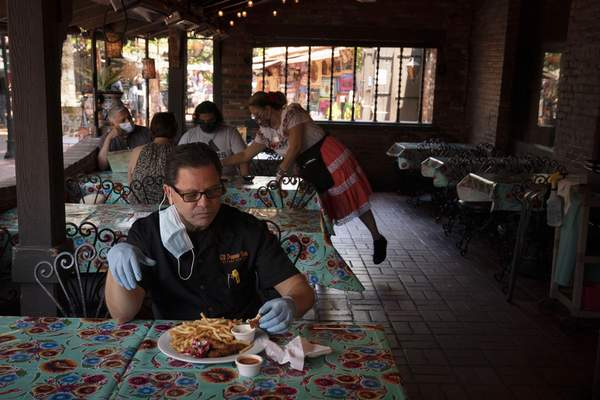 Everardo Gallegos, one of managers at El Paseo Inn Mexican restaurant on Olvera Street, eats his lunch at the restaurant with his protective gloves on in Los Angeles, Friday, June 4, 2021. (AP Photo/Jae C. Hong)