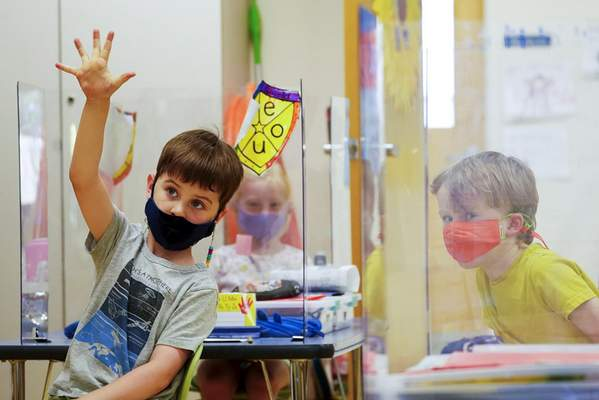 FILE - In this May 18, 2021, file photo, kindergarten students wear masks and are separated by plexiglass during a math lesson at the Milton Elementary School, in Rye, N.Y. (AP Photo/Mary Altaffer, File)
