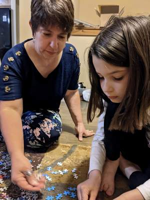 In this photo provided by Christina Neu, Christina Neu works on a puzzle with her six-year-old daughter Charissa Wednesday, June 9, 2021, in Wichita, Kan. (Christina Neu via AP)
