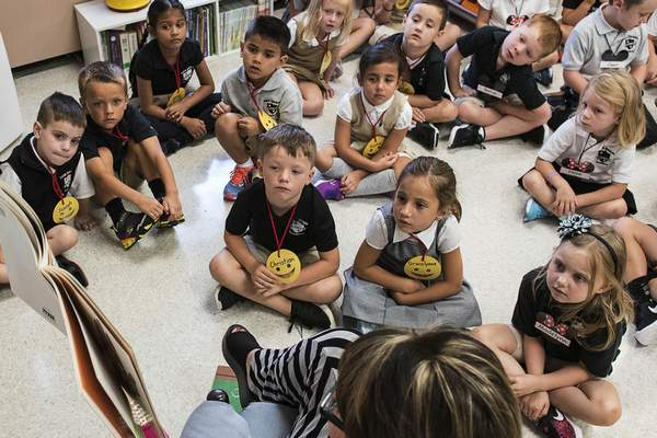 FILE †In this Aug. 22, 2018, file photo, students from two kindergarten classes at the Lewiston elementary campus of Saint Dominic Academy, listen to a teacher read a book, in Lewiston, Maine. (Russ Dillingham/Sun Journal via AP, File)