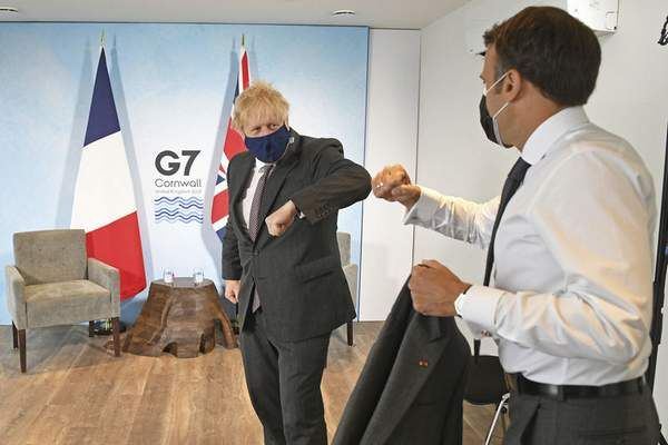 Britain's Prime Minister Boris Johnson, left, greets French President Emmanuel Macron ahead of a bilateral meeting during the G7 summit in Cornwall, England, Saturday June 12, 2021. (Stefan Rousseau/Pool via AP)