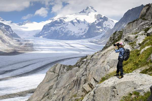 FILE - In this July 21, 2020 file photo, Swiss photographer David Carlier takes photographs of the Swiss Aletsch glacier, the longest glacier in Europe, in Fieschertal, Switzerland. (Laurent Gillieron/Keystone via AP, File)
