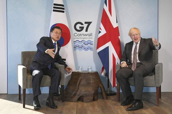 Britain's Prime Minister Boris Johnson, right, sits with South Korea's President Moon Jae-in, ahead of a bilateral meeting during the G7 summit in Carbis Bay, southern England, Sunday June 13, 2021. (Stefan Rousseau/Pool via AP)