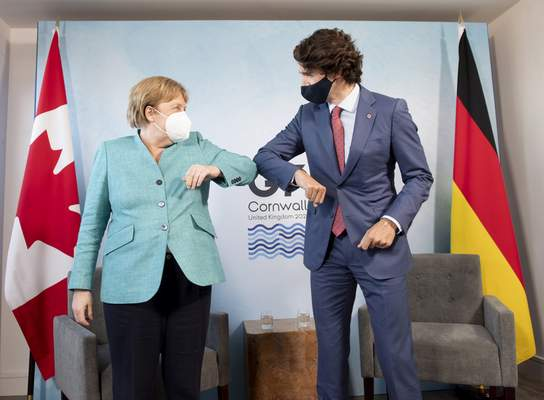 Canadian Prime Minister Justin Trudeau welcomes German Chancellor Angela Merkel at the start of a bilateral meeting at the G7 Summit in Carbis Bay, Cornwall, England, Saturday, June 12, 2021. (Adrian Wyld/The Canadian Press via AP)
