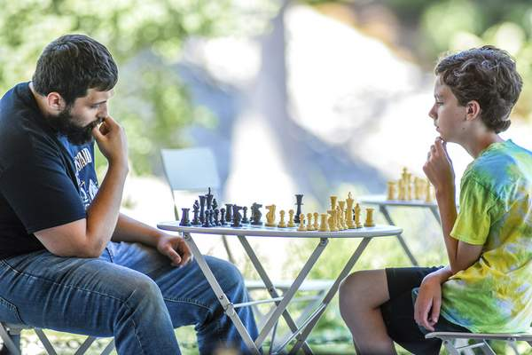 Photos by Mike Moore   The Journal Gazette Chris Jacobs, left and Toby Watson, 12, face off during a free community chess event Sunday at Promenade Park downtown.