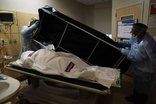 Virus Outbreak 600k FILE - In this Jan. 9, 2021 file photo, transporters Miguel Lopez, right, Noe Meza prepare to move a body of a COVID-19 victim to a morgue at Providence Holy Cross Medical Center in the Mission Hills section of Los Angeles. The U.S. death toll from COVID-19 has topped 600,000, even as the vaccination drive has drastically slashed daily cases and deaths and allowed the country to emerge from the gloom. (AP Photo/Jae C. Hong, File) (Jae C. HongSTF)
