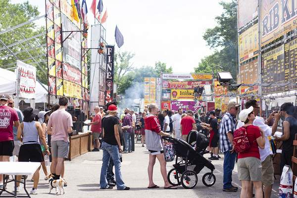 Photos by Katie Fyfe | The Journal Gazette Scores of visitors wait in line Saturday at the numerous booths at Saturday's BBQ Ribfest at Headwaters Park.