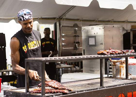 Katie Fyfe | The Journal Gazette Marlan Thomas with Cowboys Barbeque & Rib Company serves up a slab during BBQ Ribfest at Headwaters Park on Saturday.