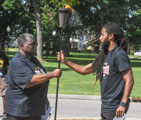 Photos by Michelle Davies | The Journal Gazette  Zynette Paige, left, passes a torch representing the power, responsibility and burden of leadership to Adrian Curry at a celebration of Juneteenth on Saturday at Weisser Park.