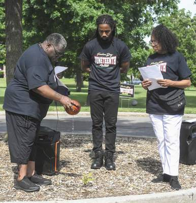 Michelle Davies | The Journal Gazette Zynette Paige, left, annoints the ground to remember and honor those who came before, with Adrian Curry, center, and Chief Condra Ridley, right, looking on. The annointing was part of the celebration of Juneteenth.