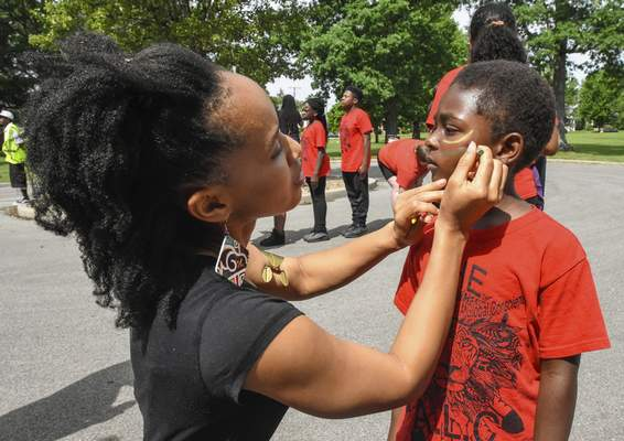 Volunteer Réna Bradley decorates the face  of Làbella Jones, 5, a member of ALC, before the start of Saturday's parade for the celebration of Juneteenth that started at Weisser Park.