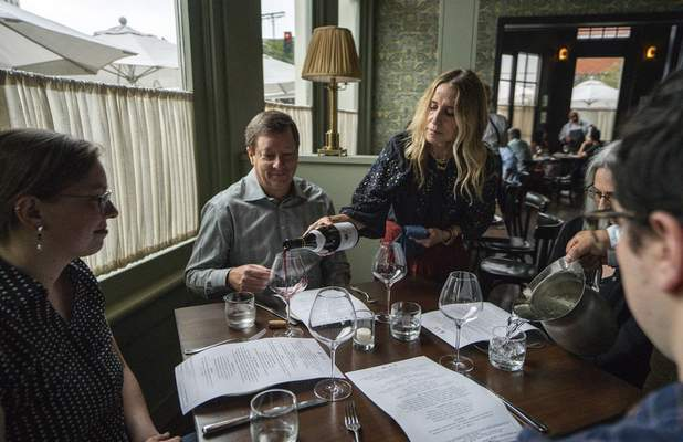 In this Saturday, June 19, 2021, photo, Caroline Styne, owner and wine director at The Lucques Group, serves wine to attorney Alec Nedelman, celebrating early Father's Day with his family at the A.O.C. Brentwood restaurant in Los Angeles. (AP Photo/Damian Dovarganes)