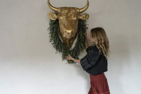 In this Saturday, June 19, 2021, photo, Caroline Styne, owner and wine director at The Lucques Group, hangs a fresh floral wreath decoration to welcome customers, while her staff readies for arriving customers at the A.O.C. Brentwood restaurant in Los Angeles. (AP Photo/Damian Dovarganes)