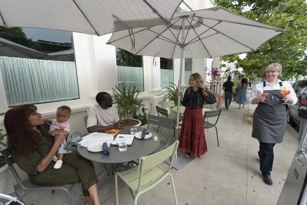 In this Saturday, June 19, 2021, photo, Caroline Styne, owner and wine director at The Lucques Group, standing under umbrella, welcomes back regular customers, Chris Anokute with his wife Jasmine and their 9-month-old son, Phoenix, at the A.O.C. Brentwood restaurant in Los Angeles. (AP Photo/Damian Dovarganes)