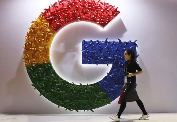 FILE - In this Monday, Nov. 5, 2018 file photo, a woman walks past the logo for Google at the China International Import Expo in Shanghai. (AP Photo/Ng Han Guan, File)