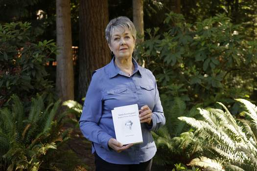 Virus Outbreak Associated Press Karen McKnight of Sammamish, Wash., holds two books written by her brother Ross Bagne of Cheyenne, Wyo., who died of COVID-19 this month at 68. He had not been vaccinated. (John FroschauerFRE)