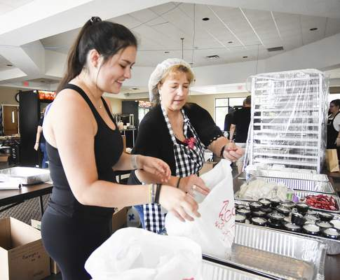 Katie Fyfe | The Journal Gazette Elizabeth Martine, left, and Kathy Retzios put orders together Saturday during Greek Fest at Holy Trinity Greek Orthodox Church. See story on Page 1C.