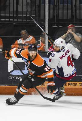 Katie Fyfe   The Journal Gazette  Komets forward Matthew Boudens chases the puck with South Carolina's Zach Malatesta close behind him during the first period at Memorial Coliseum on Wednesday.