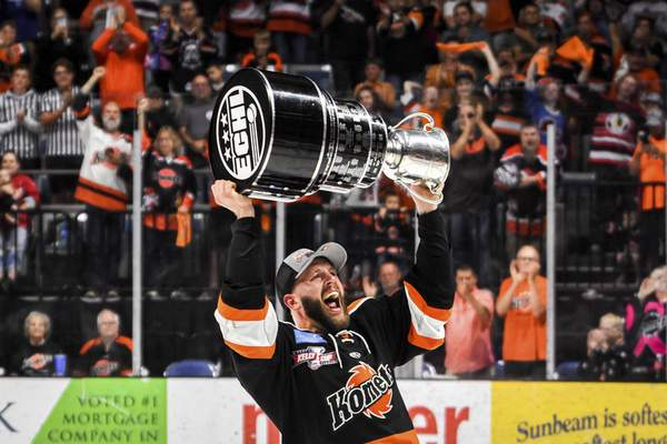 Mike Moore | The Journal Gazette Komets forward Shawn Szydlowski holds up the Kelly Cup Championship trophy in front of a sold out crowd at Memorial Coliseum on Friday.