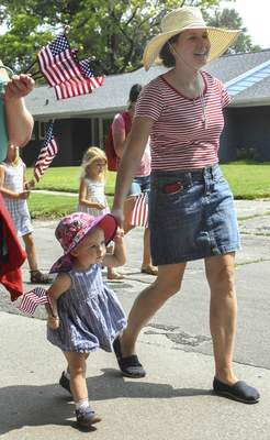 Annie Binversie, 16 months, holds her mother Sherry's hand while walking along the parade route on Old Mill Road.