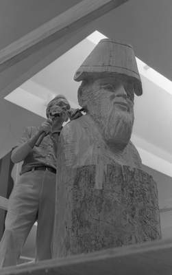 ArtistDean Butlercarves Johnny Appleseed out of an 12-foot log at Glenbrook Square in June 1976. (Journal Gazette file photo)