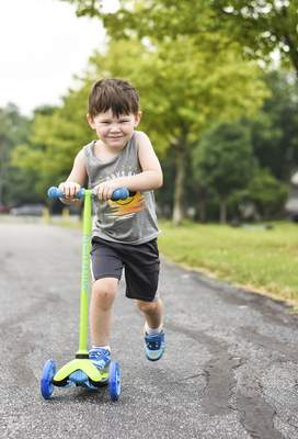 Katie Fyfe   The Journal Gazette  Jaxon Shea, 3, rides his scooter during his sister's baseball game at Hamilton Park on Tuesday.