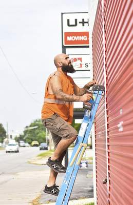 Katie Fyfe   The Journal Gazette  Al Bland fixes the siding along U-Haul Moving & Storage of Downtown Tuesday morning.