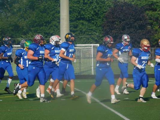 VICTORIA JACOBSEN | The Journal Gazette  The North All-Stars, including James Arnold of South Adams (center, in the helmet with a star) jog during warmups ahead of the IFCA North-South All-Star Classic at Anderson University on Friday.