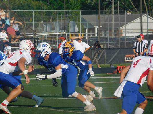 VICTORIA JACOBSEN | The Journal Gazette  Homestead linebacker Luke Palmer, center in the yellow helmet, plays in the IFCA North-South All-Star Classic at Anderson University on Friday.