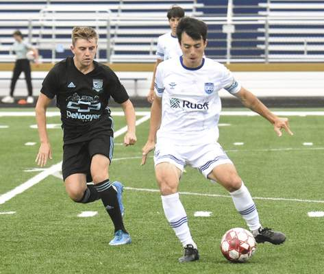 Michelle Davies | The Journal Gazette  Zach Tom, of Fort Wayne FC, looks to send the ball down the field with Kalamazoo FC's Daire O'Riordan staying close in the first half of Sunday's game at Shields Field.
