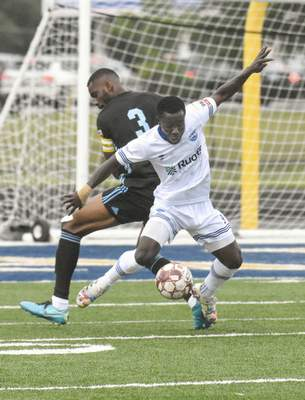 Michelle Davies | The Journal Gazette  Max Amoako, of Fort Wayne FC, works to turn the ball with Kalamazoo FC's Paul Efang in the first half of Sunday's game at Shields Field.