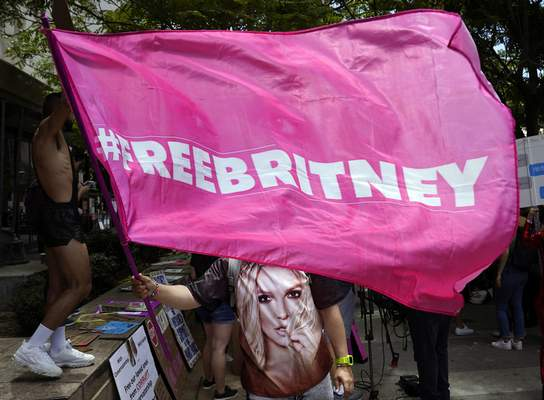 A Britney Spears supporter waves a Free Britney flag outside a court hearing concerning the pop singer's conservatorship at the Stanley Mosk Courthouse, Wednesday, June 23, 2021, in Los Angeles. (AP Photo/Chris Pizzello)
