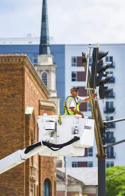 Katie Fyfe | The Journal Gazette  A worker with Fort Wayne Public Works Traffic Operations fixes traffic lights that went out at Fairfield Avenue and Wayne Street Tuesday.