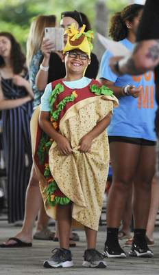 Katie Fyfe | The Journal Gazette  Dylan Durnell, 9, dresses as a Walking Taco for el Azteca Mexican Restaurant & Tequila Bar during the Waiter Waitress Contest Monday. Local restaurants sign up their best servers to compete in an obstacle course around a simulated dining room in the Festival Plaza during the Three Rivers Festival.