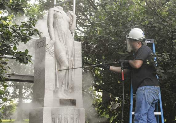 Michelle Davies | The Journal Gazette  Robert Zarycki with Conservation Sclupture & Object Studio, Inc. in Chicago, works on cleaning a statue at Memorial Park Thursday morning. The statue will be cleaned of damage from elements and graffiti and missing pieces will be recreated.