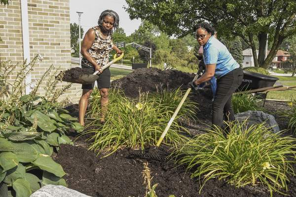 Michelle Davies | The Journal Gazette Latissha Williams, left, and Helga Portela, right, both with Unity Performing Arts Foundation, spread mulch Thursday morning at Memorial Park Middle School as part of Day of Caring sponsored by United Way of Allen County.