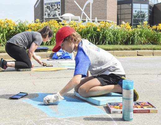 Michelle Davies | The Journal Gazette Chalk Squad member Elias Nussbaum, 10, of Ossian, works on his chalk drawing with an endangered animals theme Saturday morning at the Three Rivers Festival Chalk Walk.
