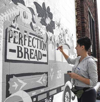 Michelle Davies | The Journal Gazette  Julie Wall of The Hedge paints a mural of a Perfection Bread truck on the side of Elysean along Fairfield Avenue Wednesday morning.