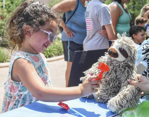 Michelle Davies | The Journal Gazette Justice Fraelich, 6, of Fort Wayne, checks the reflexes of her sloth, Big Foot, during Zoo Vet Care Day Wednesday afternoon at the Fort Wayne Children's Zoo.