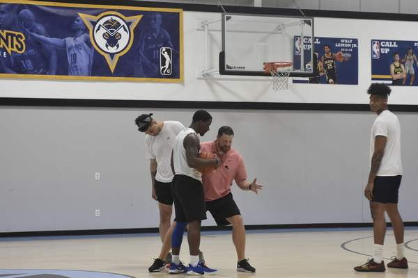 Dylan Sinn | The Journal Gazette  Fort Wayne Champs coach Steve Gansey, who coached the Mad Ants from 2015 to 2020, runs through a drill with former North Side star Trevion Crews at practice Thursday. The Champs open The Basketball Tournament tonight.