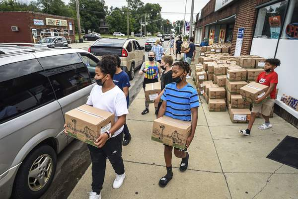 Mike Moore   The Journal Gazette Volunteers from Lakeside Middle School and North Side High School load boxes of food into cars along Oxford Street during a food giveaway Saturday.