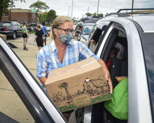 Mike Moore   The Journal Gazette Volunteer Kara Tobias spends her time Saturday by helping needy families in the community load boxes of food into their cars along Oxford Street for The Human Agricultural Cooperative, Partnership For a Healthier America project.