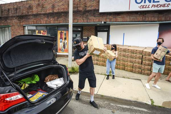 Mike Moore   The Journal Gazette Volunteers spend their time Saturday helping needy families in the community by loading boxes of food into cars along Oxford Street for The Human Agricultural Cooperative, Partnership For a Healthier America project.