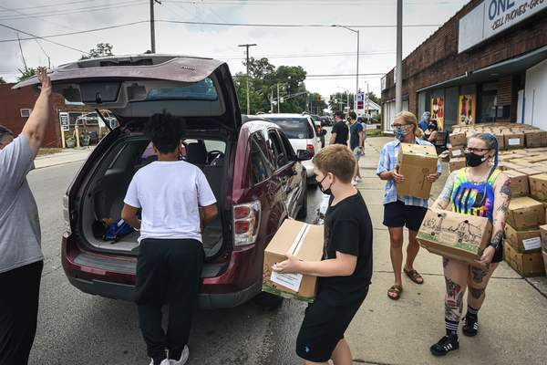 Mike Moore   The Journal Gazette Student volunteers with Lakeside Middle School and North Side High School spend their time Saturday helping needy families in the community by loading boxes of food into cars along Oxford Street for The Human Agricultural Cooperative, Partnership For a Healthier America project.