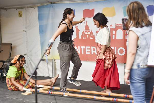 Katie Fyfe   The Journal Gazette  Izzy Carrill and Megan Buencosejo do the tinikling, a Filipino folk dance, at International Village during the Three Rivers Festival on Saturday.