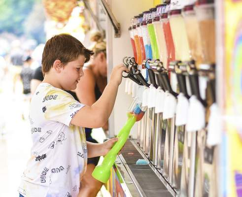 Katie Fyfe   The Journal Gazette  Declan Collins, 9, makes a slushy with his sister Finlee, 8, not pictured, at the Slush Factory in Junk Food Alley during Three Rivers Festival at Headwaters Park on Saturday.