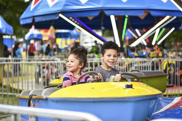 Katie Fyfe   The Journal Gazette Zian Lopez, 3, and Zyler Lopez, 7, enjoy a boat ride at the carnival during the Three Rivers Festival at Headwaters Park on Saturday.