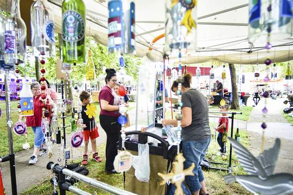 Katie Fyfe   The Journal Gazette  The Chaney family shops at Bob & Becky's Bottles at the Emporium during Three Rivers Festival at Headwaters Park on Saturday.