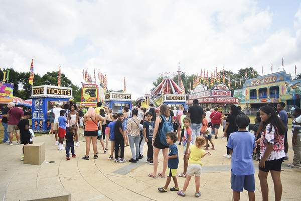 Katie Fyfe   The Journal Gazette  People line up to buy tickets at the carnival during Three Rivers Festival at Headwaters Park on Saturday.